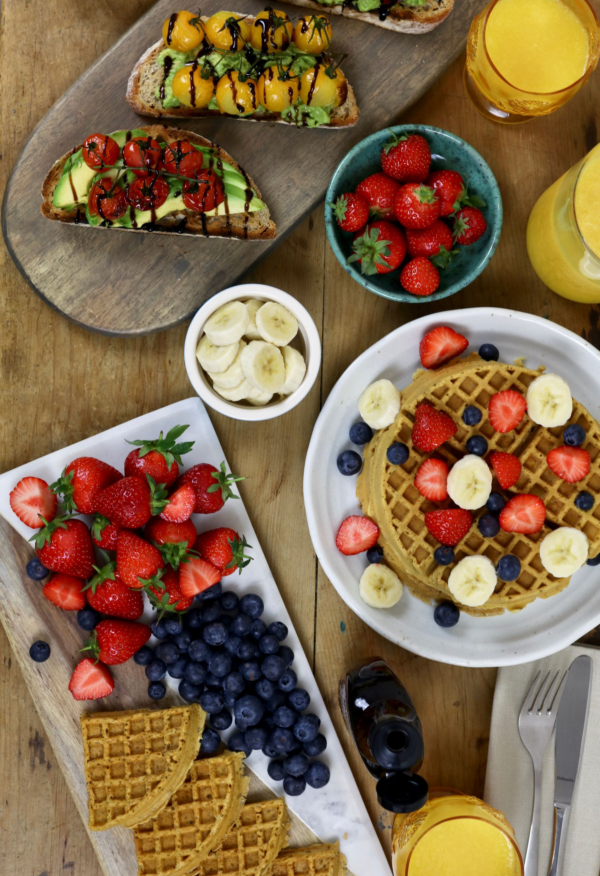 Brunch at home - vegan waffles, avocado toast, strawberries and blueberries