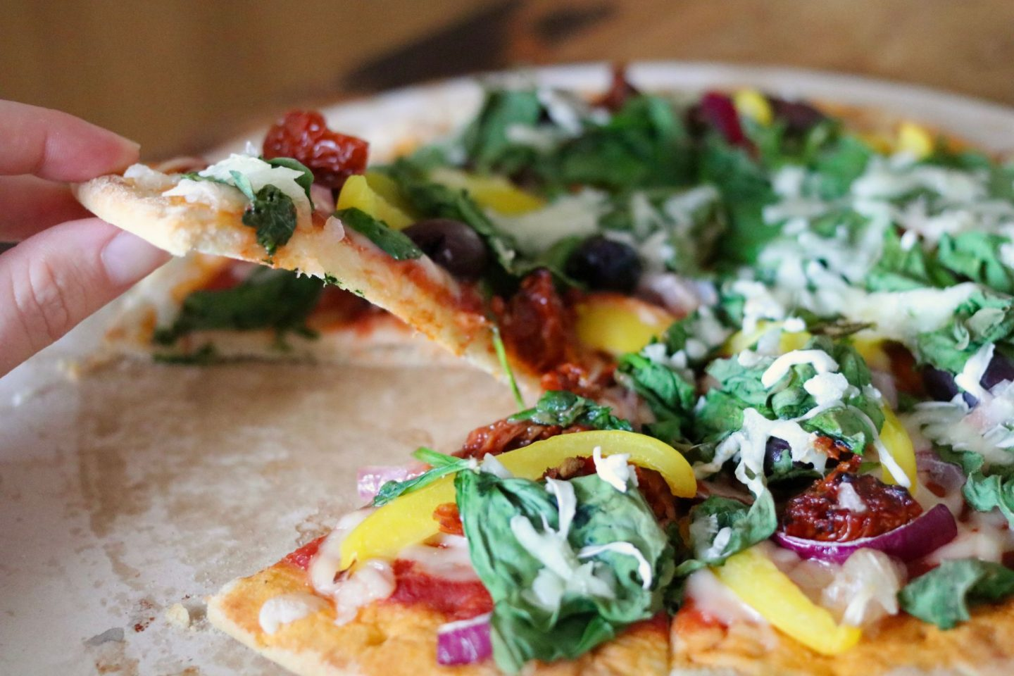 Create Your Own Vegan Pizza - picking up a slice of pizza